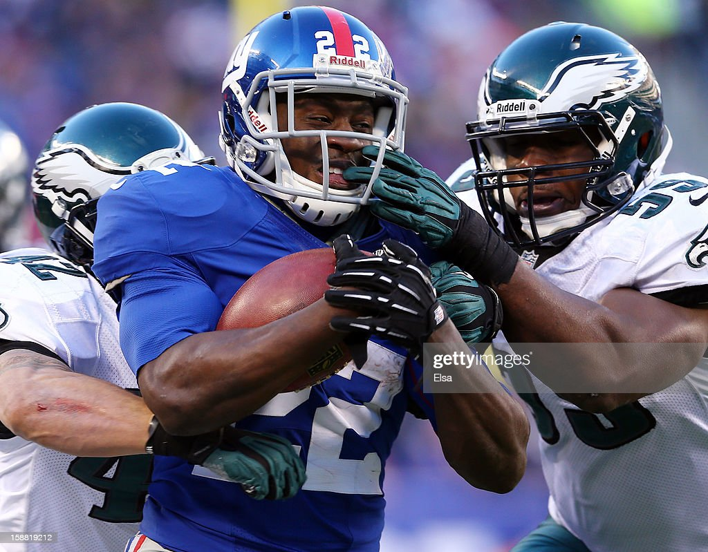 David Wilson #22 of the New York Giants carries the ball as DeMeco Ryans #59 and Kurt Coleman #42 of the Philadelphia Eagles tackle at MetLife Stadium on December 30, 2012 in East Rutherford, New Jersey. The New York Giants defeated the Philadelphia Eagles 42-7.