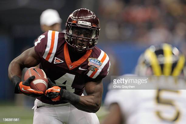David Wilson of the Virginia Tech Hokies runs with the ball against Courtney Avery of the Michigan Wolverines during the Allstate Sugar Bowl at...