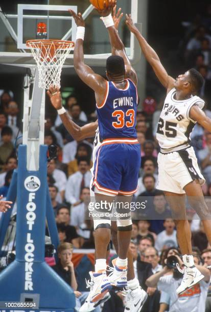 David Wingate of the San Antonio Spurs leaps to defend the shot of Patrick Ewing of the New York Knicks during an NBA basketball game circa 1989 at...