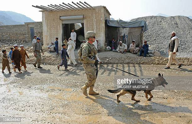 David Winners with SSG Fama sniffer dog from US army HHB 3-7 Field Artillery Regiment 3rd Bct 25th ID during a mission in Turkham Nangarhar,...
