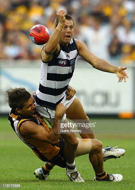 David Wojcinski of the Cats handballs whilst being tackled by Chance Bateman of the Hawks during the round five AFL match between the Hawthorn Hawks...