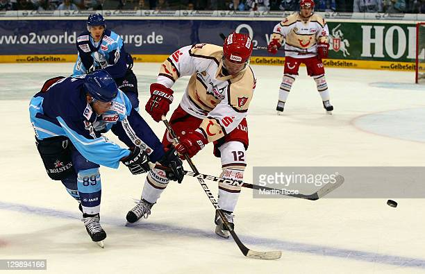 David Wolf of Hamburg battles for the puck with Christoph Herperger of Hannover during the DEL match between Hamburg Freezers and Hannover Scorpions...