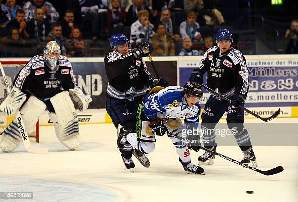 David Wolf of Hamburg battles for the puck with Michael Endrass of Straubing during the DEL match between Hamburg Freezers and Straubing Tigers on...