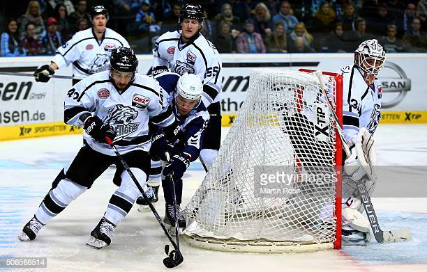 David Wolf of Hamburg Freezers battles for the puck with Marco Pfleger of Thomas Sabo Ice Tigers during the DEL game between Hamburg Freezers and...