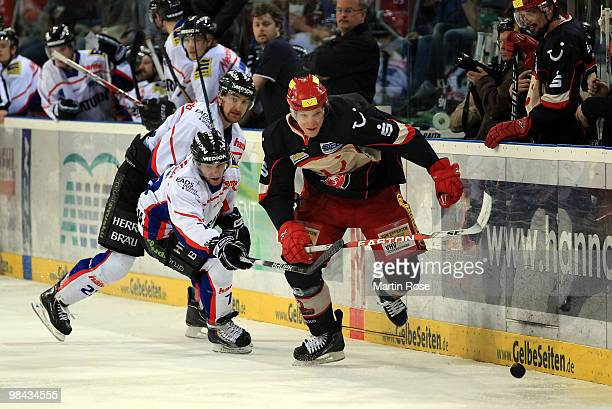 David Wolf of Hannover and Carl Corazzini of Ingolstadt battle for the puck during the third DEL play off semi final match between Hannover Scorpions...