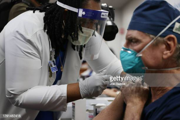 David Woosley, MD at the Jackson Health Systems, receives a Pfizer-BioNtech Covid-19 vaccine from Carol Biggs, CNO at Jackson Memorial Hospital on...