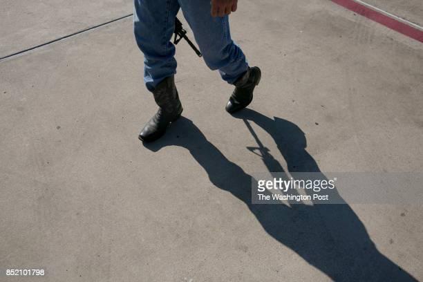 David Wright carries an AR 15 through the parking lot