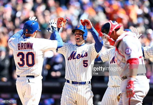 David Wright celebrates with teammate Andrew Brown of the New York Mets after Brown hit a three run homer in the first inning as Wilson Ramos of the...