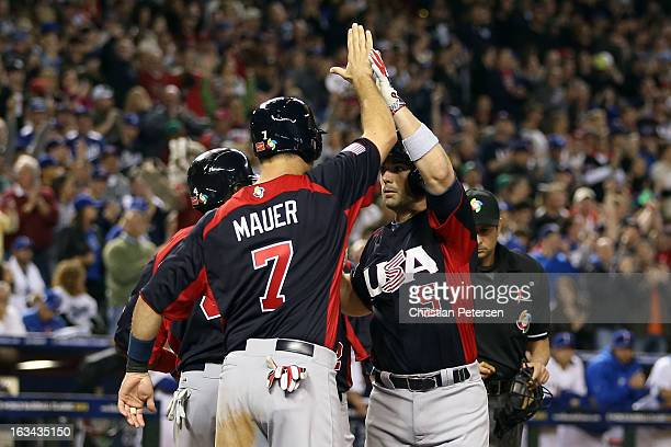 David Wright of Team USA celebrates with his teammates Joe Mauer and Brandon Phillips after hitting a Grand Slam in the fifth inning against Matt...