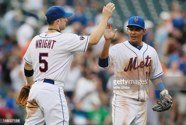 David Wright of the New York Mets celebrates with teammate Ruben Tejada after defeating the Chicago Cubs at Citi Field on July 7 2012 in the Flushing...