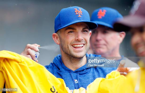 David Wright of the New York Mets reacts to being sprayed by a teammate in retaliation for his prank as he has the rain coat he got from a security...