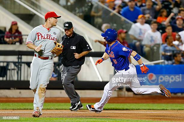 David Wright of the New York Mets rounds third base past Cody Asche of the Philadelphia Phillies to score a run in the fourth inning at Citi Field on...