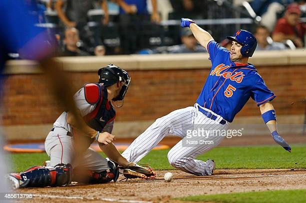David Wright of the New York Mets scores as he slides in to home on an RBI triple by Michael Cuddyer in the fifth inning against catcher Blake...