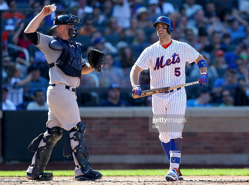 David Wright #5 of the New York Mets walks back to the dugout past Brian McCann #34 of the New York Yankees after Wright struck out with bases loaded in the seventh inning during interleague play on September 19, 2015 at Citi Field in the Flushing neighborhood of the Queens borough of New York City.
