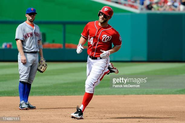David Wright of the New York Mets watches Bryce Harper of the Washington Nationals round third base after hitting a tworun home run in the third...
