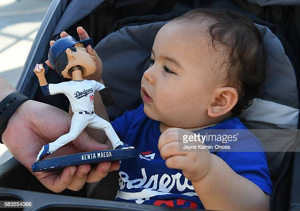 David Yasayl 10 months plays with his Kenta Maeda bobblehead as part of Japan night promotion for the game between the Los Angeles Dodgers and the...