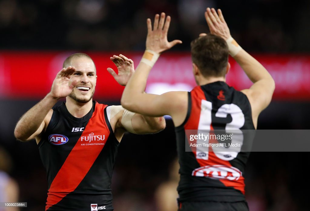 David Zaharakis of the Bombers (left) congratulates Orazio Fantasia of the Bombers on a goal during the 2018 AFL round 18 match between the Essendon Bombers and the Fremantle Dockers at Etihad Stadium on July 21, 2018 in Melbourne, Australia.