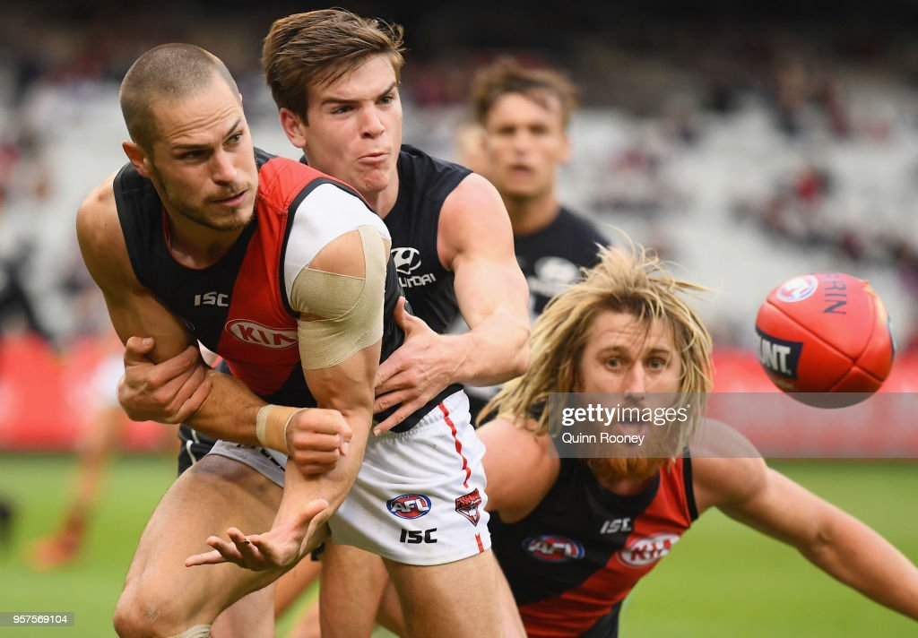 David Zaharakis of the Bombers handballs whilst being tackled by Paddy Dow of the Blues during the round eight AFL match between the Carlton Blues and the Essendon Bombers at Melbourne Cricket Ground on May 12, 2018 in Melbourne, Australia.