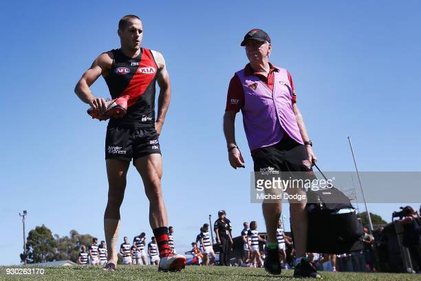 David Zaharakis of the Bombers hobbles down the race with a sore leg during the JLT Community Series AFL match between the Geelong Cats and the...