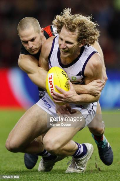 David Zaharakis of the Bombers tackles David Mundy of the Dockers during the round 23 AFL match between the Essendon Bombers and the Fremantle...