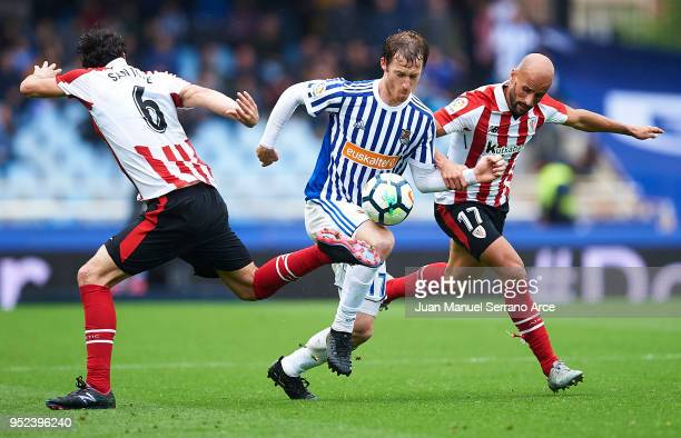 David Zurutuza of Real Sociedad bieng fouled by Mikel Rico of Athletic Club and Mikel San Jose of Athletic Club during the La Liga match between Real...