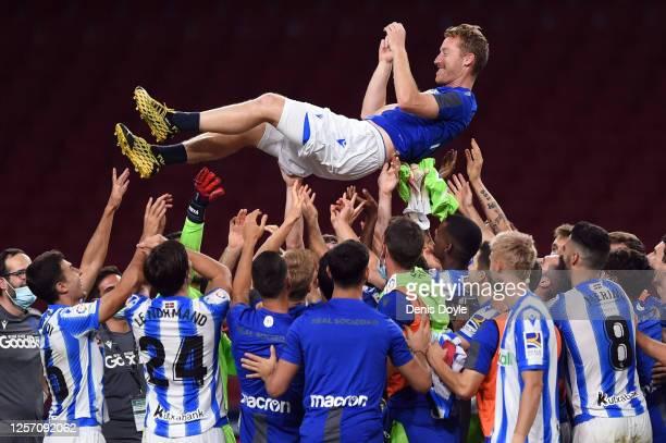 David Zurutuza of Real Sociedad is thrown in the air by his teamates after the Liga match between Club Atletico de Madrid and Real Sociedad at Wanda...