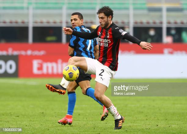 Davide Calabria of AC Milan controls the ball whilst under pressure from Alexis Sanchez of Internazionale during the Serie A match between AC Milan...