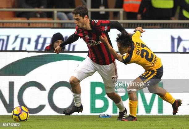 Davide Calabria of AC Milan is challenged by Woo Lee Seung of Hellas Verona FC during the Tim Cup match between AC Milan and Hellas Verona FC at...