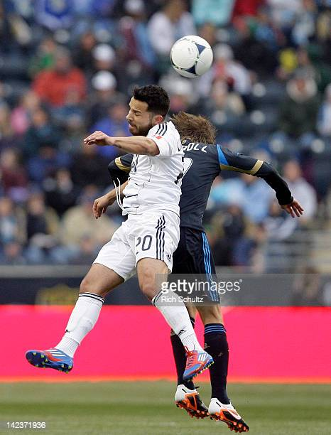 Davide Chiumiento of the Vancouver Whitecaps fights for a header with Brian Carroll of the Philadelphia Union during the first half of a Major League...