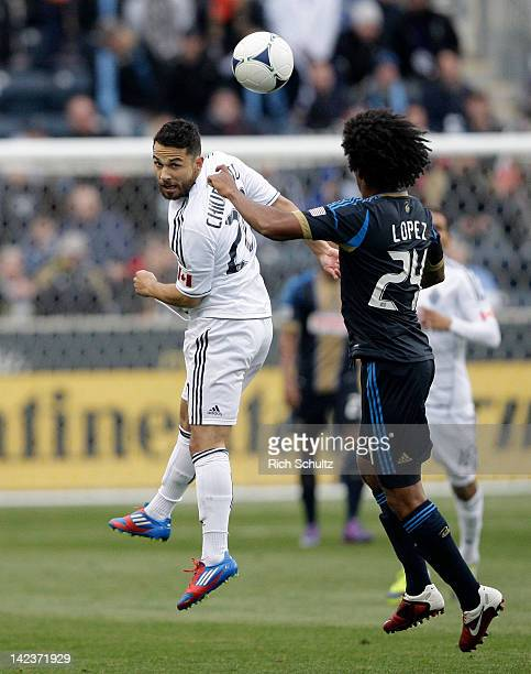 Davide Chiumiento of the Vancouver Whitecaps heads the ball away from Porfirio Lopez of the Philadelphia Union during the first half of a Major...