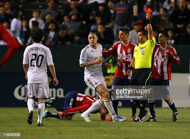 Davide Chiumiento of the Vancouver Whitecaps watches as referee Ricardo Salazar issues a red card to his fellow Whitecaps teammate Eric Hassli after...