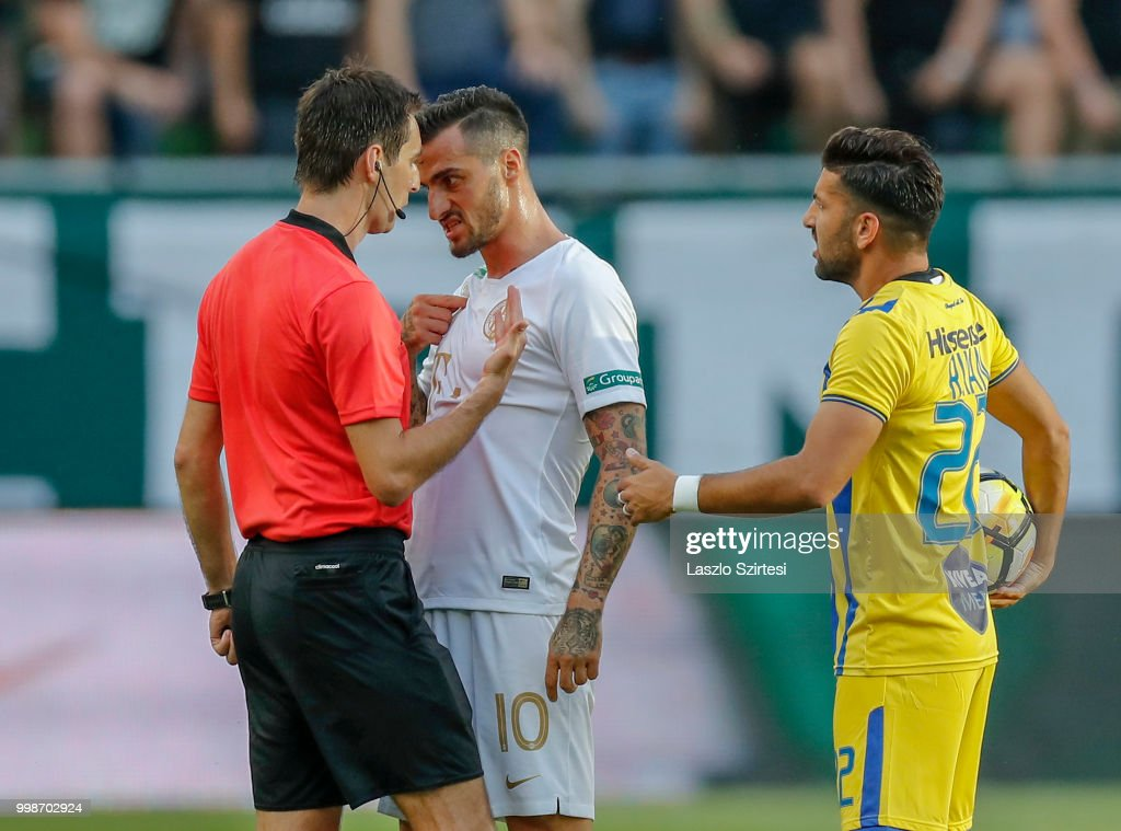 Davide Lanzafame of Ferencvarosi TC (l2) argues with referee Ricardo De Burgos (l) next to Avi Rikan of Maccabi Tel Aviv FC (r) during the UEFA Europa League First Qualifying Round 1st Leg match between Ferencvarosi TC and Maccabi Tel Aviv FC at Groupama Arena on July 12, 2018 in Budapest, Hungary.