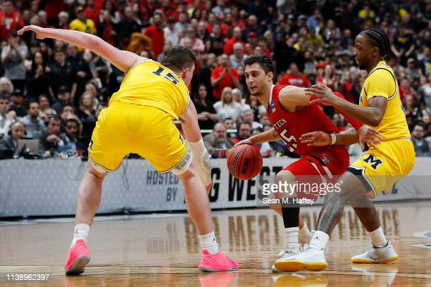 Davide Moretti of the Texas Tech Red Raiders drives against Zavier Simpson and Jon Teske of the Michigan Wolverines during the 2019 NCAA Men's...