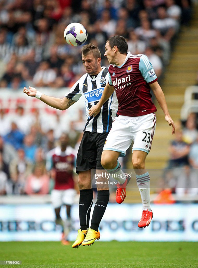 Davide Santon of Newcastle challenges Stewart Downing of West Ham during the Barclays Premiership Match between Newcastle United and West Ham United at St. James Park on August 24, 2013, in Newcastle upon Tyne, England.