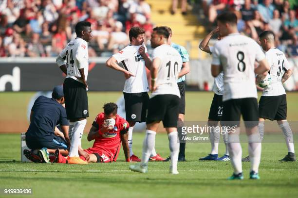 Davie Selke of Berlin receives treatment after being hit by Makoto Hasebe of Frankfurt during the Bundesliga match between Eintracht Frankfurt and...