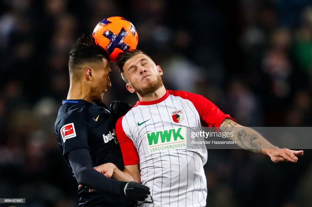 Davie Selke #27 of Hertha Berlin (L) and Jeffrey Gouweleeuw #6 of Augsburg battle for the ball during the Bundesliga match between FC Augsburg and Hertha BSC at WWK-Arena on December 10, 2017 in Augsburg, Germany.