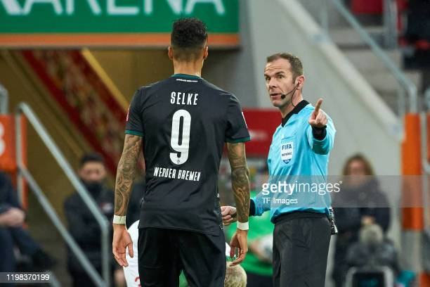 Davie Selke of SV Werder Bremen speaks with referee Marco Fritz during the Bundesliga match between FC Augsburg and SV Werder Bremen at WWKArena on...
