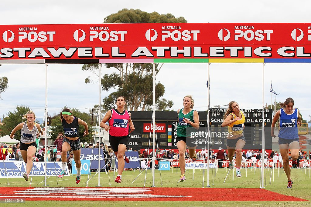 Davina Strauss (pink) crosses the line to win the State of Victoria Strickland Family Women's Gift 120m Final during the 2013 Stawell Gift carnival at Central Park on April 1, 2013 in Stawell, Australia.