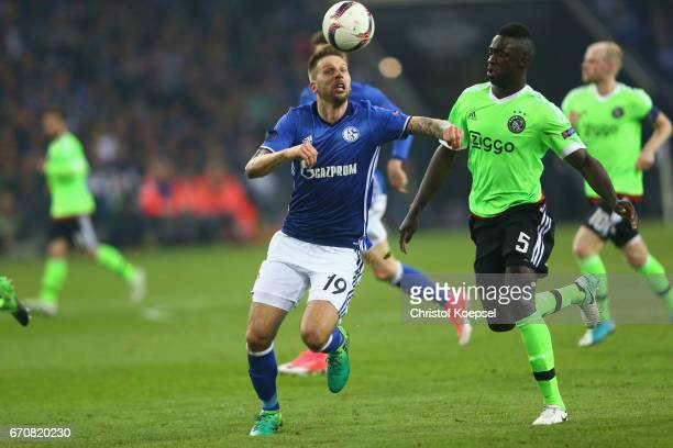 Davinson Sanchez of Amsterdam challenges Guido Burgstaller of Schalke during the UEFA Europa League quarter final second leg match between FC Schalke...
