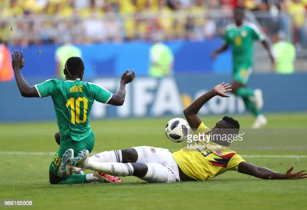 Davinson Sanchez of Colombia slides in to tackle Sadio Mane of Senegal for incident that was reviewed to VAR with no penalty awarded during the 2018...