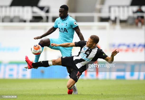 Davinson Sanchez of Tottenham Hotspur battles for possession with Dwight Gayle of Newcastle United during the Premier League match between Newcastle...