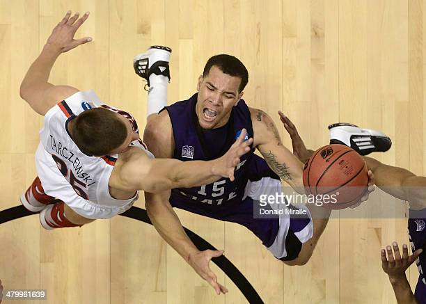 Davion Berry of the Weber State Wildcats goes up for a shot against Kaleb Tarczewski of the Arizona Wildcats during the second round of the 2014 NCAA...