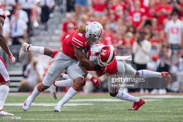 Davion Johnson of the Miami Redhawks is tackled by Chase Young and Damon Arnette of the Ohio State Buckeyes during game action between the Ohio State...