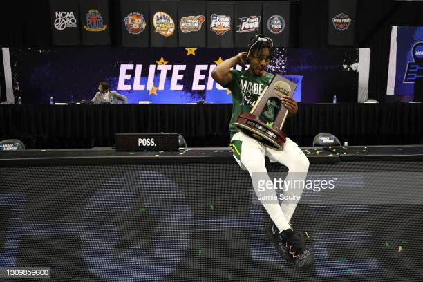 Davion Mitchell of the Baylor Bears celebrates with the trophy after defeating the Arkansas Razorbacks in the Elite Eight round of the 2021 NCAA...