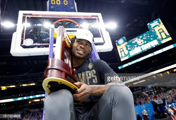 Davion Mitchell of the Baylor Bears sits on a ladder with the trophy after defeating the Gonzaga Bulldogs in the National Championship game of the...