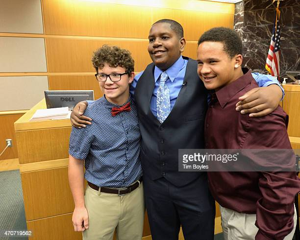 Davion Navar Henry Only poses for a photograph with his new adoptive brother Taylor Going and another friend after being adopted by his former...