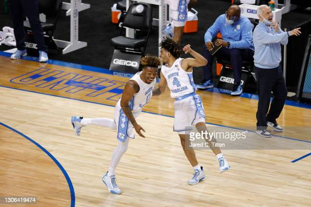 Davis and Anthony Harris of the North Carolina Tar Heels react following a dunk by Davis during the second half of their second round game against...