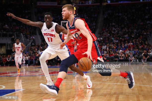 Davis Bertans of the Washington Wizards drives around Tony Snell of the Detroit Pistons during the first half at Little Caesars Arena on December 16...