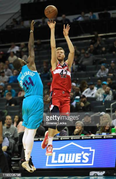 Davis Bertans of the Washington Wizards shoots over Michael KiddGilchrist of the Charlotte Hornets during their game at Spectrum Center on December...