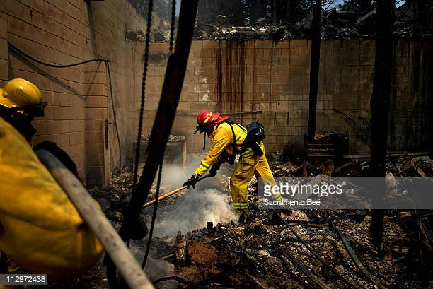 Davis fire captain Kim Jester puts out hot spots in the remains of a garage that was destroyed by the Angora Fire in South Lake Tahoe, California,...